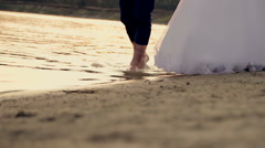Bride and groom walking barefoot  on the edge of the clear water at sunset Stock Footage