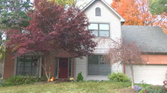 Establishing shot front of a middle class house during daytime in autumn / fall Stock Footage