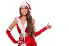 Stock Photo of Happy laughing brunette woman dressed as Santa pointing at us, isolated again