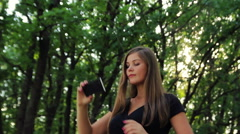 Beautiful girl doing a  self-portrait in a park in the sun Stock Footage