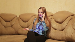On the phone home : woman swears calling in living room Stock Footage