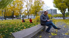 A man in a gray jacket sitting in the park on a granite bench and read e-books. Stock Footage