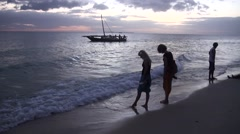 Two women at the beach of Indian's ocean coast at sunset. Tanzania - stock footage