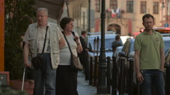 Man with crutch walking on a street in Prague Stock Footage