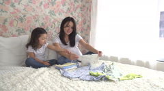 Pregnant long term Asian mother and daughter prepare clothes for the new baby Stock Footage