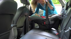 Mother place baby safety chair on car seat and fasten. 4K Stock Footage