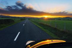country road towards Unza village at sunset with car reflections - stock photo