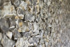 old stone wall made of flint - stock photo