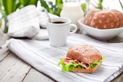 Multigrain bread roll with cup of coffee on the  table Stock Photos