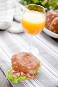 Multigrain bread roll with glass of orange juice on the table Stock Photos