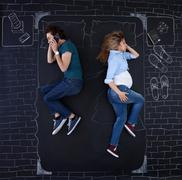 Young couple feeling relaxed in a bed drawed by chalk on paper. Stock Photos