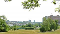 View of the large park in the suburb - in the distance city - cars pass - breeze Stock Footage