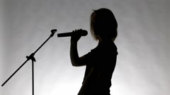 Black silhouette of a girl singing - stock footage