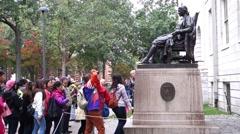 A tourist touching John Harvard statue for good luck Stock Footage