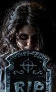 Creepy latina teen girl with tombstone - stock photo