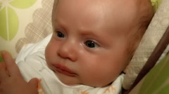Close up video of infant Caucasian Baby Boy sitting in rocking chair and smiling Arkistovideo