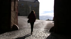 Lady walking through archway inside the grounds of Varberg Fortress in Sweden Stock Footage