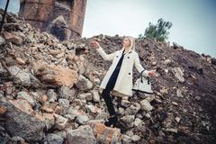 Blonde in the coat on the ruins of the house, beauty - stock photo