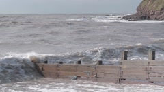 Large Murky Brown Waves Breaking over Sea Defences in Stormy Weather Stock Footage