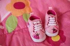 Pink shoes for little baby girl - stock photo