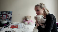 Girl sitting on the bed and cuddling a teddy bear Stock Footage
