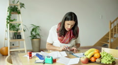Stock Video Footage of Woman working on documents and calculate something on smartphone