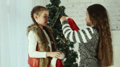 Two girls wear Santa hats to one another - stock footage
