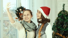 Two teenage girlfriends doing selfie on the background Christmas tree - stock footage