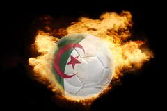 football ball with the flag of algeria on fire - stock photo