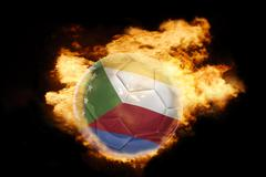 football ball with the flag of comoros on fire - stock photo