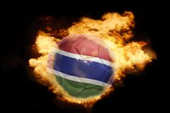 Stock Photo of football ball with the flag of gambia on fire