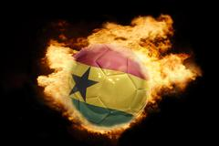 football ball with the flag of ghana on fire - stock photo