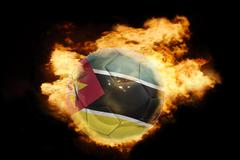 Stock Photo of football ball with the flag of mozambique on fire