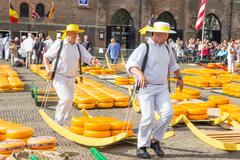 Carriers walking with many cheeses in the Alkmaar market Stock Photos