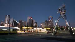 Dallas skyline twiligh time-lapse w/ Dart station traffic & statue Stock Footage