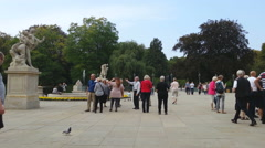 Group of tourists taking pictures on square in historic part of European city Stock Footage