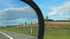 Car driving on highway, view from passenger seat. Fields and forest on roadside Stock Footage