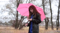 Stock Video Footage of The woman with phone in a raincoat