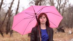 Stock Video Footage of The woman with a pink umbrella costs in the rain