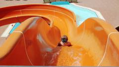 Young Boy Riding On Orange Water Slide To The Pool. Aquapark, Water Park - stock footage