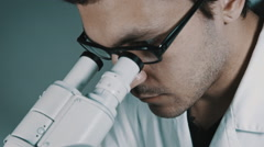 Young doctor  looking through the microscope - stock footage