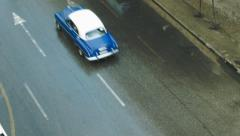 Classic cars driving in the rain in Havana Stock Footage