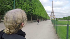Woman Views Eiffel Tower from Champs de Mars Pan Around Stock Footage