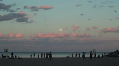 Beach scene at dusk with moon and beach goers in silhouette Stock Footage