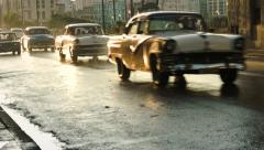 Row of classic cars driving in golden hour sunset in Havana Stock Footage