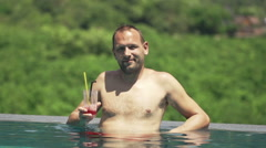 Young man raising toast to camera and drinking cocktail in pool Stock Footage