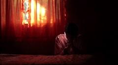 Man praying in sunbeam next to bed - stock footage