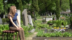 sad woman visit relatives graves in country cemetery. 4K - stock footage