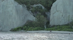 People on beach cove dwarfed by bluffs Stock Footage