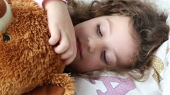 A little girl resting on the couch with a teddy bear, closeup, tracking shot Stock Footage